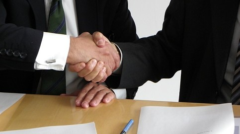 dos personas firmando un convenio